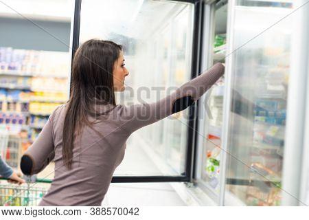 Woman taking deep frozen food from a freezer in a spuermarket