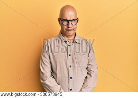 Middle age bald man wearing casual clothes and glasses skeptic and nervous, frowning upset because of problem. negative person.