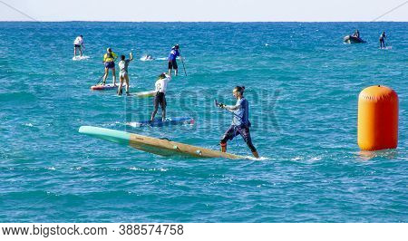 04 Oct 2020: Garraf, Spain. Stand Up Paddle Surfing Or Sup Race Competition. Man Makes Buoy Turn. Pe