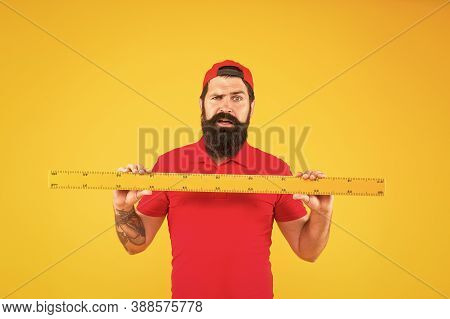 Shop Assistant. Perfect Size. Bearded Man With Big Measuring Instrument. Measuring With Ruler. Size