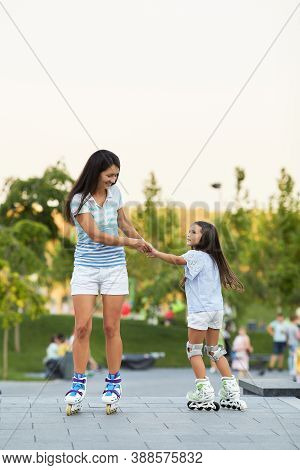 Smiling Mother And Her Little Daughter Rollerskating In Summer Park In Sunny Day