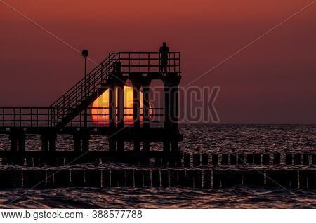 Sunset - A Man On The Seashore Observes A Natural Phenomenon
