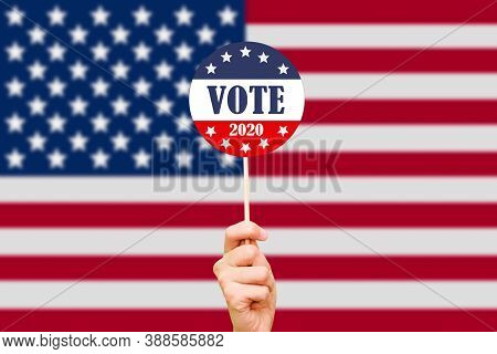 Hand And Button For Voting In Elections On The Background Of The American Flag. The 2020 Us Presiden