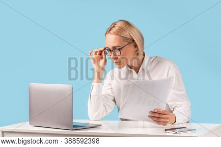 Female Office Employee Looking Through Documents, Making Report, Doing Paperwork Near Laptop At Her