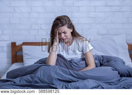 Psychological Health Care Concept. Portrait Of Lonely Stressed Young Woman Sitting Alone In Her Bed,