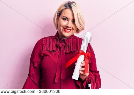 Beautiful blonde plus size woman holding graduated degree diploma over pink background looking positive and happy standing and smiling with a confident smile showing teeth