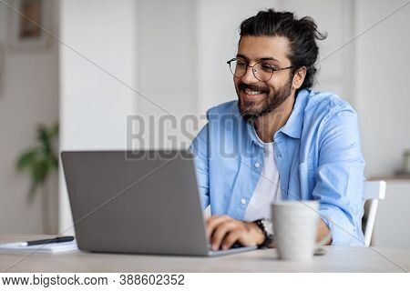 Young Indian Male Writer Using Laptop Computer, Sitting At Desk In Home Office, Handsome Western Man
