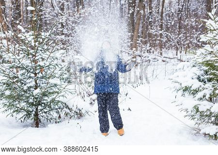 Cute Young Boy Plays With Snow, Have Fun, Smiles. Teenager In Winter Park. Active Lifestyle, Winter