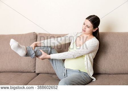 Leg Cramps During Pregnancy. Closeup Of Hands Massaging Swollen Foot While Sitting On Sofa