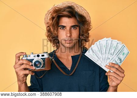 Young hispanic man holding vintage camera and dollars relaxed with serious expression on face. simple and natural looking at the camera.
