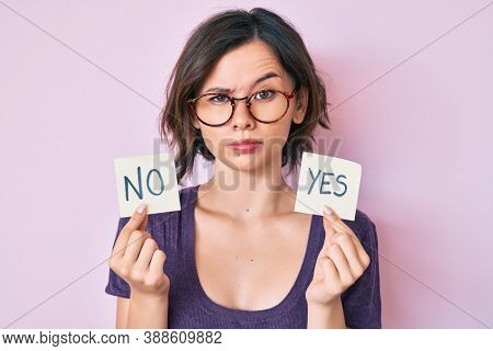 Young beautiful girl holding yes and no reminder skeptic and nervous, frowning upset because of problem. negative person.