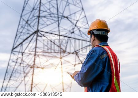 Electrical Engineer Wear Safety Clothes Standing And Watching At The Electric Power Station To View