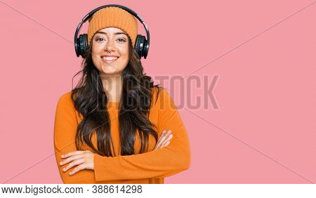 Beautiful brunette young woman listening to music using headphones happy face smiling with crossed arms looking at the camera. positive person.