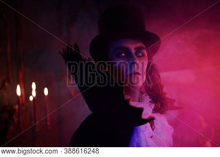 Portrait of vampire standing the night in an old castle on smoky background. Traditional vampire man. Halloween. Count Dracula.