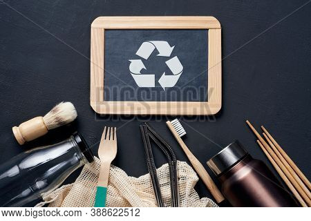 a pile of no-plastic sustainable household items, such as refillable metal and glass bottles, shopping mesh bags, or wooden toiletries, cutlery and chopsticks, and the recycling symbol in a chalkboard