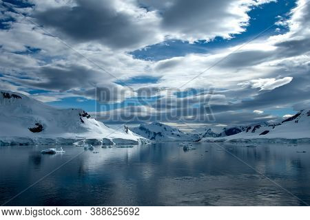 Icebergs And Dramatic Skies And Extreme Terrain In Antarctica.