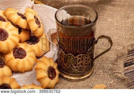 Homemade Pastry Cookies With Jam And A Faceted Glass Of Tea In A Vintage Cup Holder On A Background