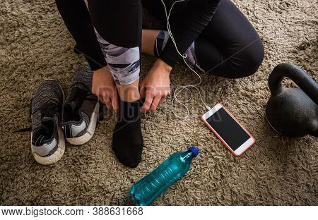 Blonde Woman Getting Dressed For Workout With Weights