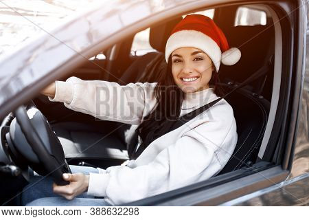 Happy New Year And Merry Christmas A Woman Is Sitting In A Car, She Is Wearing A Red Santaclaus Hat