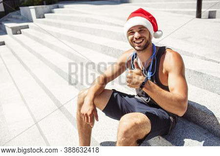 Young Man Exercising Outside. Guy Wearing Christmas Santa Hat And Show Big Thumb Up. Like Symbol. St
