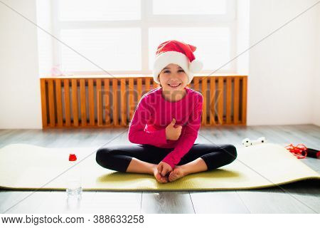 Thumbs Up Merry Christmas And A Happy New Year Little Girl Workout At Home In Santa Christmas Hat .