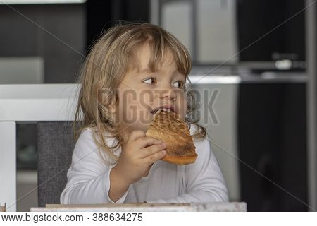 Little Girl Eating Pizza In The Kitchen, Sitting At The Table. Dessert For The Child 2.