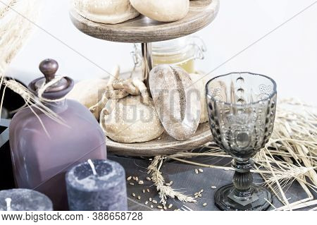 Baked Pasty Or Bread On Wooden Tray Near Glass Bocal And Candle With Spikelet Laying On Table With N