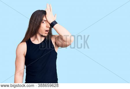 Young adult man with long hair wearing goth style with black clothes surprised with hand on head for mistake, remember error. forgot, bad memory concept.