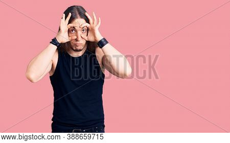 Young adult man with long hair wearing goth style with black clothes trying to open eyes with fingers, sleepy and tired for morning fatigue