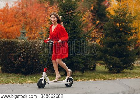 Young Woman With Electric Scooter In Red Dress At The Autumn City Park