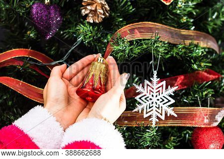 Hands Holding Christmas Ornament In Front Of Christmas Tree. Decorating Fir Branches With Christmas
