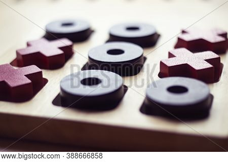 Wooden Tic Tac Toe Game On White Background. Red Crosses And Black Noughts. Closeup Photo