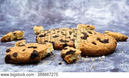 One Soft Freshly Baked Chocolate Chip Cookie With Crumbs And Chunks On A Gray Marble Kitchen Counter