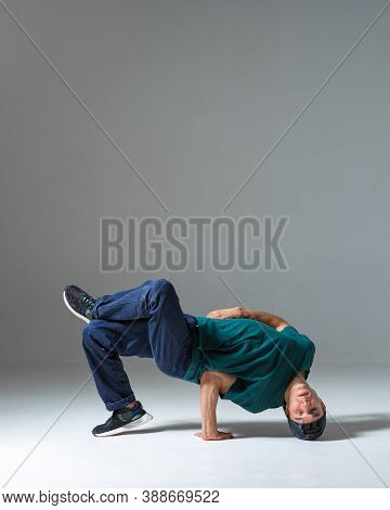 Young Guy Breakdancer Dancing On The Floor Isolated On Gray Background. Breakdance Lessons