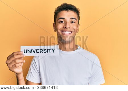 Young handsome african american man holding paper with university word looking positive and happy standing and smiling with a confident smile showing teeth