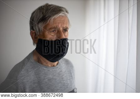 Senior man wearing  a facemask during coronavirus and flu outbreak. Virus and illness protection, home quarantine. COVID-19 concept