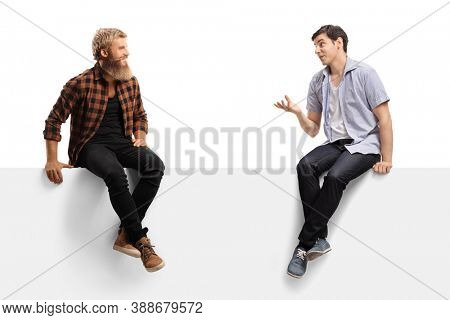Two young men sitting on a blank panel and talking isolated on white background