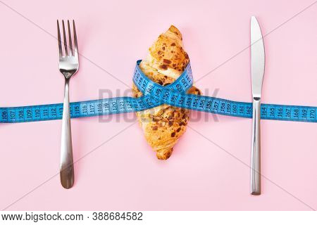 A Baked Almond Croissant Wrapped In A Measuring Tape On A Pink Background. The Concept Of Diet, Anti