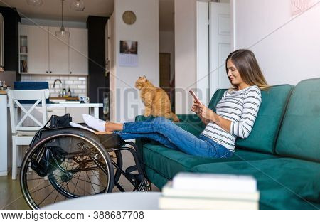 Disabled young woman using smartphone while sitting on sofa at home