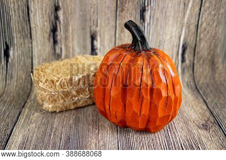 Colorful Pumpkin And A Hey Stack Isolated On The Wood Background. Thanksgiving Content