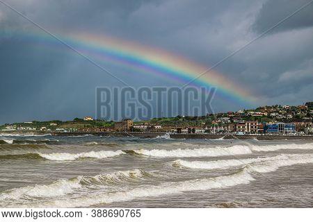 Dramatic Coastal Landscape With Rainbow. Beutiful Rainbow Against Dark Stormy Sky In Gijon, Asturias