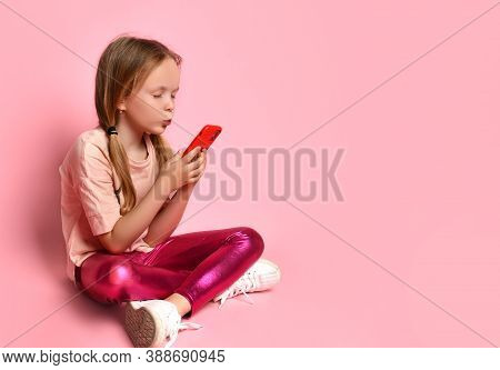 Blonde Little Girl In A T-shirt, Leggings And Sneakers. She Kisses The Screen Of Her Red Smartphone,