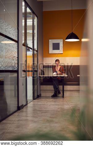Businesswoman Working Late In Open Plan Office Using Laptop