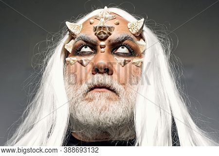 Bearded Old Man Dressed Like Halloween Monster. Wizard Demon Man With Dragon Skin And Horns. Man Evi