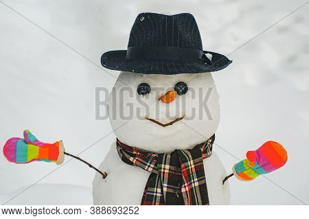 Funny Snowman With A Carrot Instead Of A Nose And In A Warm Knitted Hat On A Snowy Meadow On A Blurr