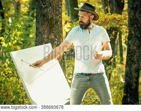 Art Concept. Painting In Nature. Start New Picture. Painter With Easel And Canvas. Bearded Man Paint