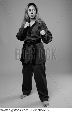 Portrait Of Young Asian Woman Wearing Karate Gi Ready To Fight