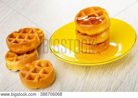 Few Waffle, Poured Honey Round Soft Waffle In Yellow Saucer On Wooden Table
