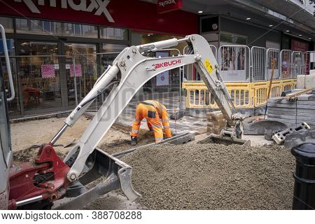 Doncaster,yorkshire, England - October 7, 2020. Hunched Worker In A Street Work Near An Excavator.