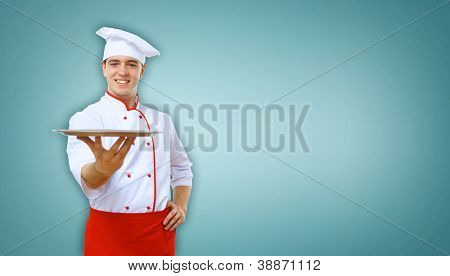 Portrait of a young male cook in red apron against colour background